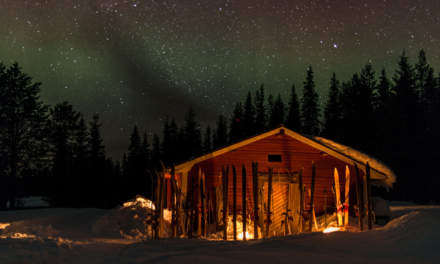 Aurora above the wooden sauna