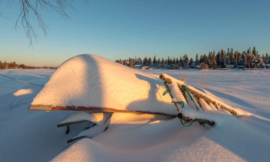 Snow covered boat at the beach of Storgrundet