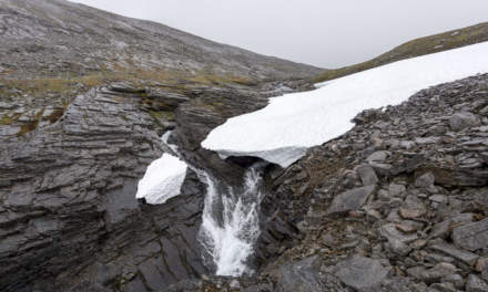 Old snow fields, rocks, a ravine and a waterfall