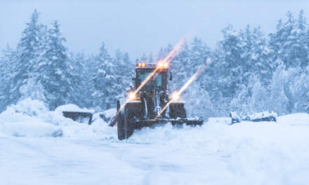 A man is clearing the snow with a shovel loader