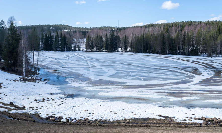 Snowmobile tracks on the melting lake