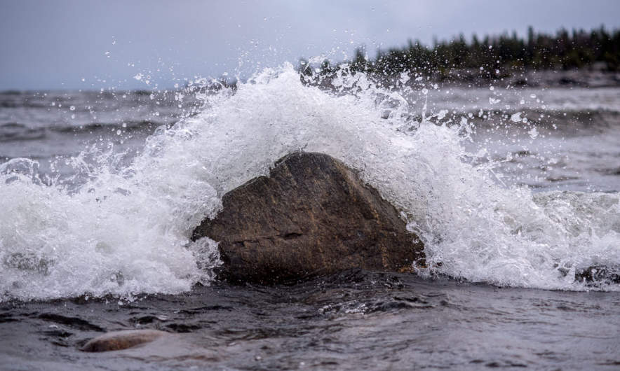 Wave splashing at a large rock.