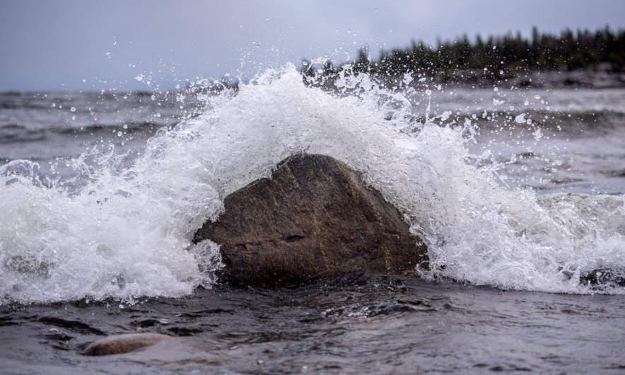 Wave splashing at a large rock.