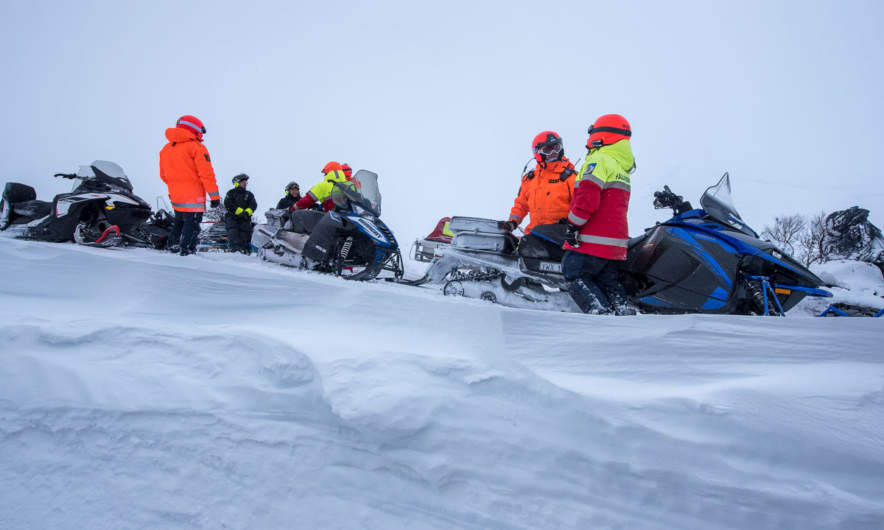Police and mountain rescue on snowmobiles