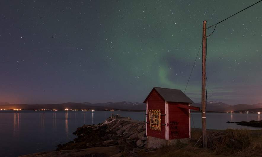 A nightly motive by the sea with a faint aurora